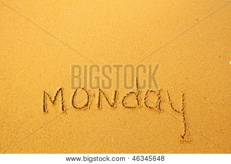 Monday - written in sand on beach texture.