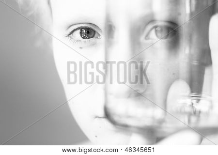 Young girl looks through the empty glass, black and white photo.