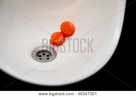 Urinal bowl with red antiseptic tablets, close-up