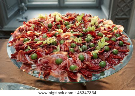 Platter with cured ham on table, catering event
