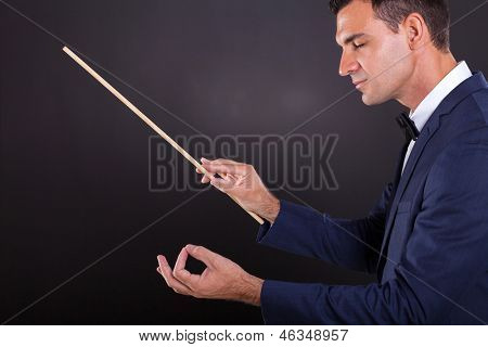 male conductor with eyes closed on black background
