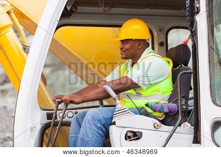 african american man operates excavator on building site