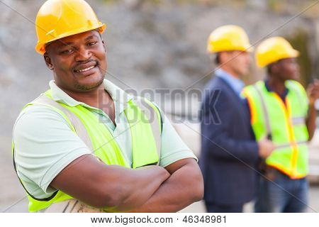 smiling african mine worker at mining site with colleagues
