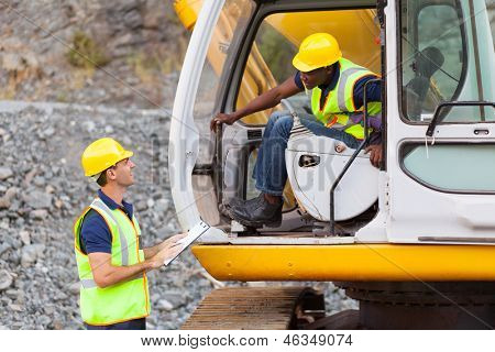 cheerful construction foreman talking to excavator operator