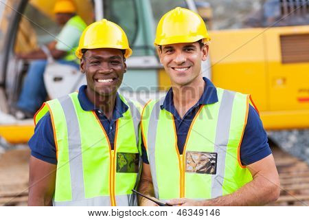 two cheerful male road construction workers on construction site