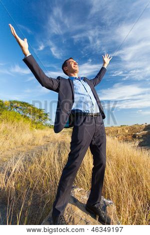excited young businessman on top of rock with arms outstretched outdoors