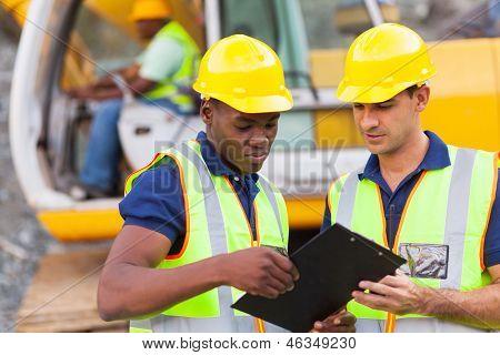 compañeros de trabajo de construcción discutiendo sobre el sitio de construcción de plan de trabajo