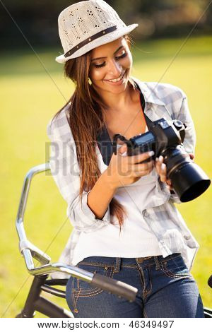 beautiful young woman reviewing photos on digital camera outdoors