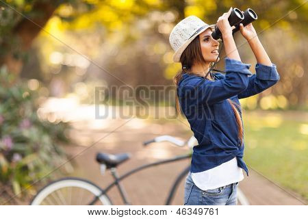 attractive young woman using binoculars bird watching at the park