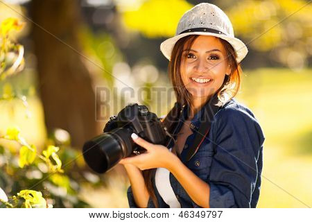 beautiful female student photographer with her camera at the park
