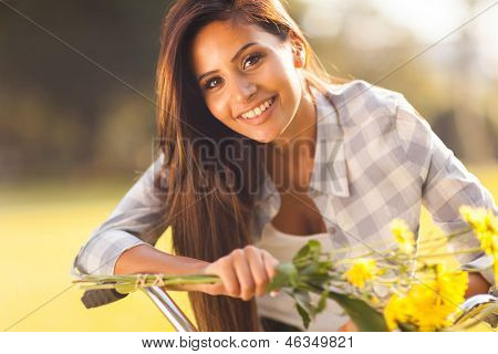 happy beautiful young woman with flowers riding a bike