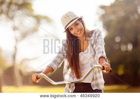 beautiful young woman riding a bicycle outdoors