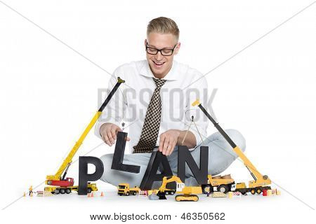 Build up a plan concept: Joyful businessman building the word plan along with construction machines, isolated on white background.