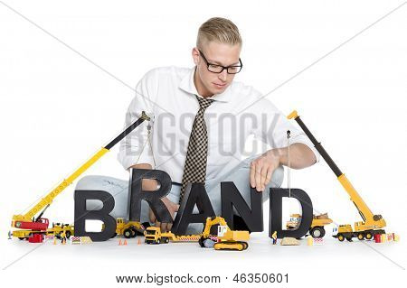 Build up a brand concept: Smiling businessman building the word brand along with construction machines, isolated on white background.