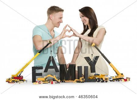 Starting a family concept: Loving young couple holding hands in heart shape along with construction machines building the word family, isolated on white background.