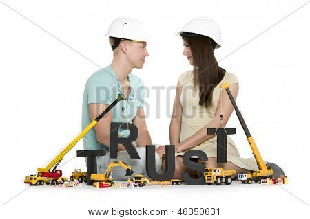 Building up trust concept: Smiling young man and woman along with construction machines establishing the word trust, isolated on white background.