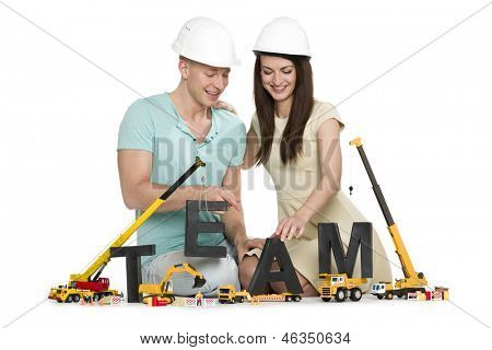 Team building concept: Joyous young man and woman building the word team along with construction machines, isolated on white background.