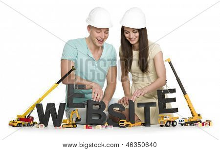 Website under construction concept: Cheerful man and woman building the word website along with construction machines, isolated on white background.
