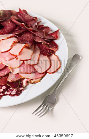 sliced sausages and ham on a plate