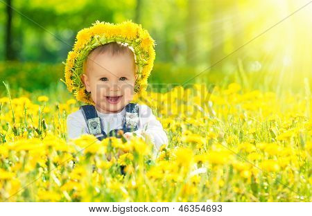 Happy Baby Girl In A Wreath On  Meadow With Yellow Flowers  On The Nature