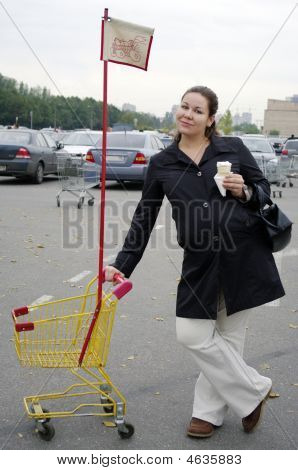 Pregnant Woman With Shopping Trolley And Ice Cream.