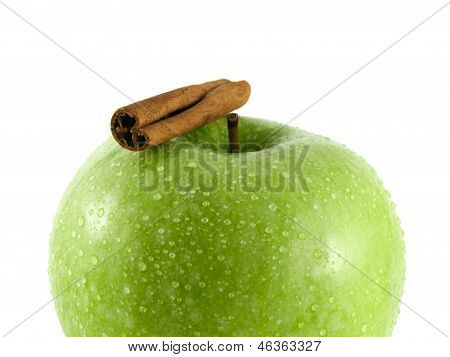 Isolated green apple with cinnamon pods on white