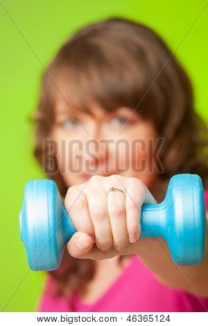 Woman doing exercise with dumb bell, strengthen her arms and shoulders over green background