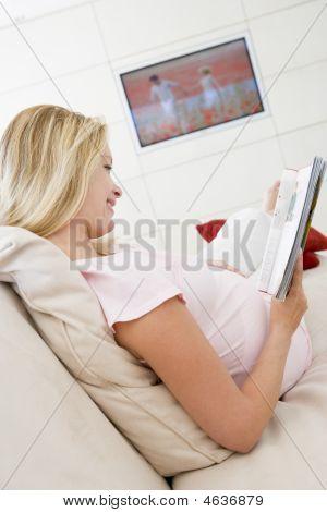 schwangere Frau lesen Magazin mit Fernsehen in Hintergrund lächelnd
