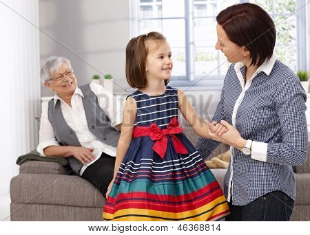 Adorable little girl and mother talking, granny watching from behind.