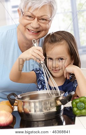 Grandmother and little granddaughter cooking at home, smiling.