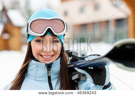 Close up of female wearing sports jacket and goggles who hands skis