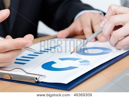 Close up view of hands of business people sitting at the table with documents, white background