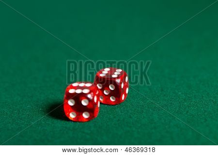 Two red dices on the poker table. Risky entertainment of gambling