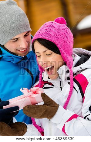 Close up of man giving present to woman outdoors during winter holidays