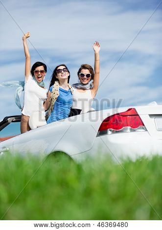 Group of girls stands in the cabriolet with hands up. Happy journey of joyful teenagers