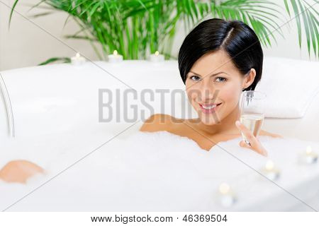 Mulher tomando banho com espuma e velas bebe álcool e relaxa
