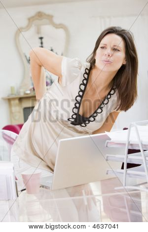 Pregnant Woman In Home Office With A Sore Back