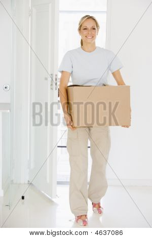Woman With Box Moving Into New Home Smiling