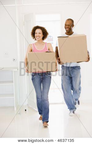 Pareja con cajas en nuevo hogar sonriendo