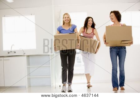 Three Girl Friends Moving Into New Home Smiling