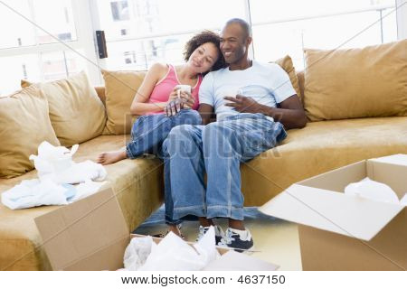 Couple Relaxing With Coffee By Boxes In New Home Smiling