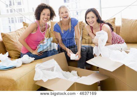 Três amigos de menina desembalar caixas na nova casa sorrindo