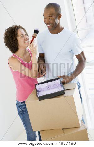 Casal com rolo e pintura em nova casa sorrindo