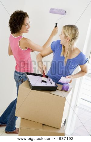 Two Women Painting Room In New Home Smiling