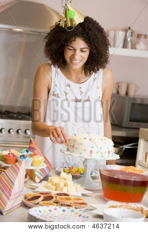 Woman At Party Fixing Cake On Table Smiling