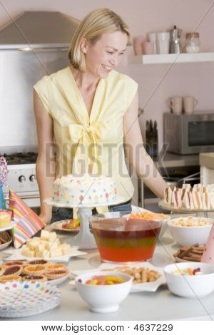 Woman At Party Standing By Food Table Smiling