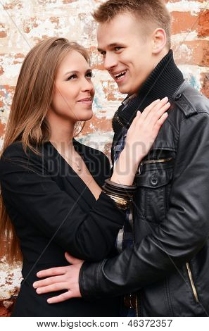Young enamoured pair at a brick wall
