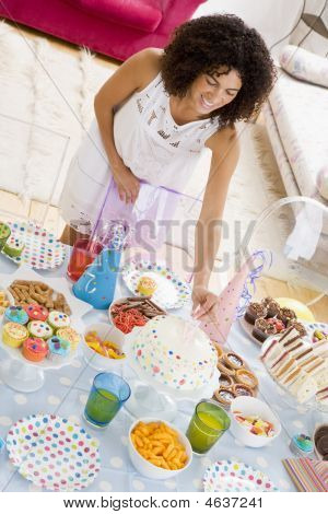 Woman At Party Putting Candles In Cake On Food Table Smiling