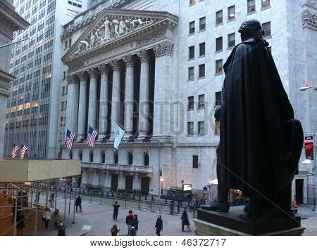 NEW YORK - MAY 13: From Federal Hall, pedestrians walk along Broad Street past the New York Stock Exchange on May 13, 2013 in New York City. The Exchange building was built in 1903.