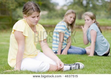 Duas meninas Bullying outra jovem ao ar livre
